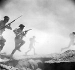 Australian soldiers running toward the front lines during re-enactment of the Battle of El Alamein, 24 Oct 1942