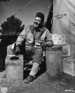 American Red Cross assistant field director Herbert M. Sifford grinding coffee in a camp near Tebessa, Tunisia before heading out to meet soldiers, 19 Feb 1943