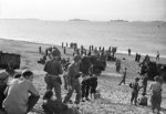 British sailors and British and American soldiers on the beach at Algiers, mid-Nov 1942; note 40-mm Bofors gun and three trucks in background