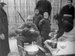 Japanese soldier dining among Chinese civilians, Nanjing, China, 15 Dec 1937