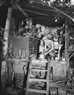 US Army Private First Class George Chapman and Sergeant John Eppard working at the Mobile Machine Shop truck of 741st Ordnance Company, 41th Infantry Division at Horanda, New Guinea, 9 May 1943