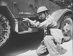 An ethnically Chinese soldier of the US Army posing with a Thompson sub-machinegun next to a halftrac armored car, Fort Knox, Kentucky, United States, Jun 1942