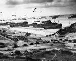 LSTs landing vehicles and cargo on a Normandy beach, June 1944, photo 1 of 2