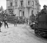 British Universal Carriers with deep wading screens and a Churchill AVRE tank passing through La Breche, France, 6 Jun 1944
