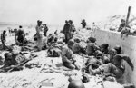 Americans of the 4th Infantry Division being tended by US Medical Corpsmen by a sea wall at Utah Red Beach, Normandy, France, morning of 6 Jun 1944