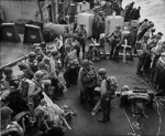 American soldiers in full combat gear on the deck of an United States Coast Guard assault transport in the English Channel, off Normandy, France, 6 Jun 1944