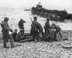 American troops administered first aid to the survivors of sunken landing craft, Normandy, 6 Jun 1944; note LCT-29 in background