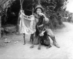 US Marine Corporal Harold Flagg and his war dog Boy posing with a Japanese flag, Okinawa, Japan, Apr 1945. Note the battle dressing on the dog