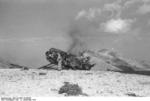 German airborne trooper destroying a crash-landed glider, Gran Sasso, Italy, 12 Sep 1943