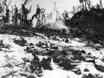 US Marines waiting in their foxholes as others blast a Japanese held cave in the nearby hill, Peleliu, Palau Islands, late Sep or early Oct 1944
