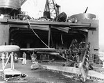 Damage to hangar doors of seaplane tender USS Curtiss by Japanese 250kg bomb during Pearl Harbor attack, 7 Dec 1941, photo 1 of 2; note wreckage of OS2U-2 floatplane in foreground