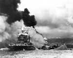 USS Maryland burning in foreground and USS Oklahoma capsizing in the back