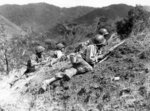 US 25th Division squad leader pointing at a suspected Japanese position at the edge of Baleta Pass, near Baguio, Luzon, Philippine Islands, 23 Mar 1945