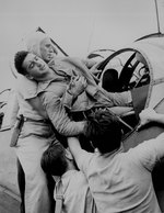Gunner Kenneth Bratton, wounded in the knee by shrapnel, being pulled out of the turret of a TBF Avenger aircraft aboard USS Saratoga after a successful raid on Rabaul, New Britain, 5 Nov 1943