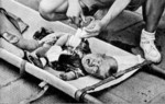 A boy scout tending to a toddler injured by Japanese bombing at South Station, Shanghai, China, 28 Aug 1937, photo 2 of 2