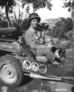 US Army Corporal Paul F. Janesk posing in his jeep in Sicily, Italy, 3 Sep 1943; note cartoon of Axis leaders drawn on his jeep, and Mussolini crossed out