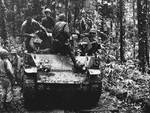 US Marines sitting atop a M3 light tank, Cape Gloucester, New Britain, Bismarck Archipelago, late Dec 1943; note fallen Japanese soldiers