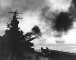 Cruiser USS Phoenix firing her 6-inch guns during the invasion of Cape Gloucester, New Britain, Bismarck Archipelago, circa 24-26 Dec 1943; note photo was taken from fantail, looking forward