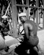 African-American men of US 34th Construction Battalion constructing prefabricated steel warehouse at Halavo Seaplane Base, Florida Island, Solomon Islands, 19 Sep 1943