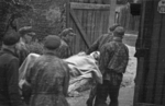 Wounded Polish insurgent fighter being evacuated from the Evangelical Cemetery, Warsaw, Poland, early Aug 1944