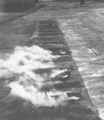 Decoy Japanese B6N, Ki-27, and other aircraft emitting false smoke during US air raid, Koshun Airfield, southern Taiwan, date unknown