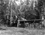 USAAF 3rd Bomb Group photographer George Tackaberry and another man with a wrecked Japanese Ki-43 fighter, Nadzab Airfield, Australian New Guinea, early 1944