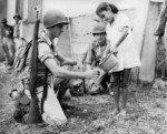 US soldier getting water from a girl during a training exercise, Panama Canal Zone, 1942