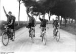 Members of Hitler Youth giving the Nazi Party salute on their bicycles, near Berlin, Germany, 1932