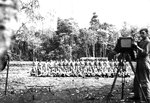 Photographer Jack Heyn of USAAF 3rd Bomb Group preparing for a group shot of airmen, Dobodura Airfield, Australian Papua, mid-1943