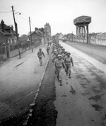 African-American soldiers of the US Army on march in Noyon, France, 28 Feb 1945