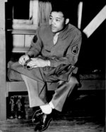 African-American boxing champion and US Army Technical Sergeant Joe Louis sewing his rank patch onto his uniform, 10 Apr 1945
