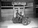 An African-American military policeman posing on his motorcycle in Columbus, Georgia, United States, 13 Apr 1942