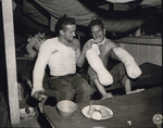 US Army Sgt. Edward F. Good feeding a fellow wounded soldier, Pfc. Lloyd Deming, a turkey leg during the Christmas dinner, 2nd Field Hospital, San Jose, Mindoro, Philippine Islands, 25 Dec 1944
