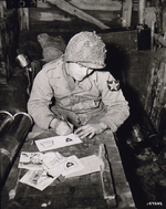 Pvt Walter Prsybyla of B Btry, 37th Field Artillery Regt, US 2nd Inf Div writing Christmas cards for friends and family from an artillery ammunition storehouse, Heckhalenfeld, Germany, 30 Nov 1944