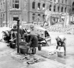 German women doing their washing at a cold water hydrant on the street in Berlin, Germany, 3 Jul 1945; note the knocked out German SdKfz. 223 vehicle in background