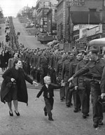 Canadian boy chasing after his father, a member of the Canadian Army British Columbia Regiment, who was on march in New Westminster, British Columbia, Canada, 1 Oct 1940