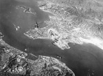 Smoke rising from Kowloon, Hong Kong, 16 Oct 1944; note Japanese fighter chasing the USAAF bomber from which this photo was taken