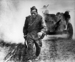 A Soviet soldier walking along a road in Russia, 1 Aug 1943; note field gun in background