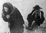 Old Russian woman pulling a man on a sled, Leningrad, Russia, date unknown