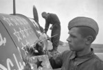 A Soviet mechanic working on a fighter aircraft while a crew member stenciled a star on the fuselage, Russia, date unknown