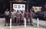 Several US Navy officers posed by a facility sign on Tulagi, Solomon Islands, circa 1945