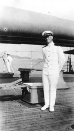 Ensign Burke posing by the 14-inch guns of USS Arizona, 1923