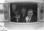 German pilot Christiansen, American pilot Schildhauer, and others at an open window of a Do X flying boat before making a trans-Atlantic flight from Europe to North America, Nov 1930