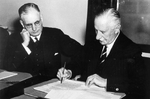 Governer General of Australia Lord Gowrie signing the declaration of war against Japan with Prime Minister John Curtin looking on, at 1115 hours, 8 Dec 1941 (2015 hours, 9 Dec 1941 local time)