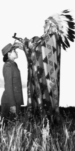 Private Mary Greyeyes (kneeling) and Councilor Harry Ball (dressed as a chief) in a propaganda photograph, Piapot, Saskatchewan, Canada, late Jun 1942