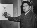 Ira Hayes with a photograph of the second flag raising on Iwo Jima, Japan, date unknown