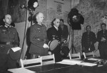 ColGen Alfred Jodl approaching the table with the documents of surrender, Reims, France, 7 May 1945. His aide, Maj Wilhelm Oxenius, is on the left and Kriegsmarine Admiral Hans-Georg Von Friedeburg is on the right