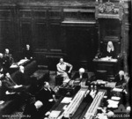 MacArthur seated next to the Speaker of the House of Representatives Mr. Nairn, Provisional Parliament House, Canberra, Australia, 1942; note Curtin seated at table