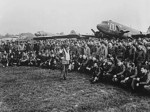 US Army Brigadier General Anthony C. McAuliffe speaking to his glider pilots, England, United Kingdom, 18 Sep 1944; note C-47 Skytrain and CG-4A glider aircraft in background