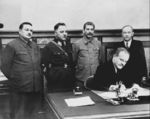 Vyacheslav Molotov signing a pact with Soviet-puppet state Finnish Democratic Republic, Moscow, Russia, 2 Dec 1939; Andrei Zhdanov, Kliment Voroshilov, Joseph Stalin, and Otoo Wille Kuusinen in background